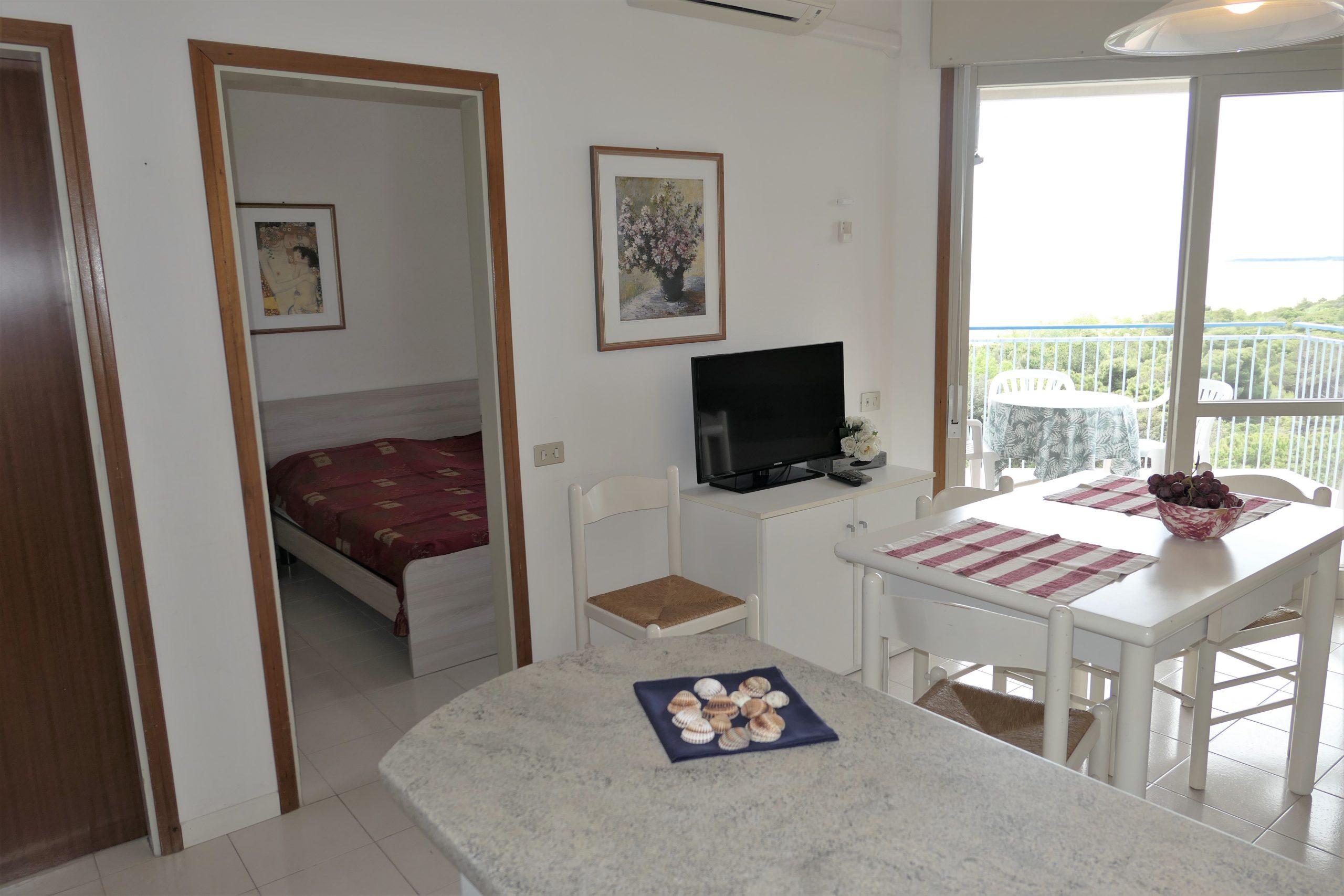 Salotto, terrazzo e camera da letto in appartamento a Lignano